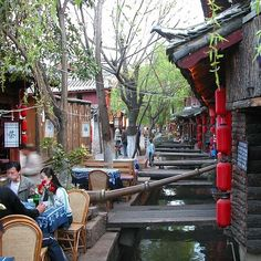 People hang out near canals and drink in the middle of the day. | 12 Reasons Lijiang Is The Prettiest City On Earth