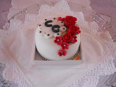 Mini Bolo coberto com pasta americana decorado com pequenas flores e as iniciais do casal. Para encomendas personalizadas acesse o link www.lejonconfeitaria.com.br