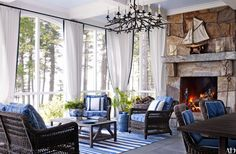 A handsome stone fireplalce, white linen drapes trimmed with cobalt blue and a bold blue and white flatweave rug bring style and energy to the enclosed porch of the Maine house by Suzanne Kasler and Les Cole.