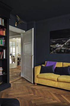 A media room and library with walls painted in Farrow & Ball Hague Blue and the woodwork in Black Blue.