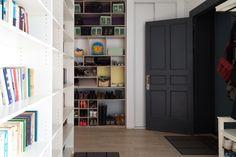 Белые стены, лаконичная мебель инебольшая домашняя библиотека вквартире для молодой семьи