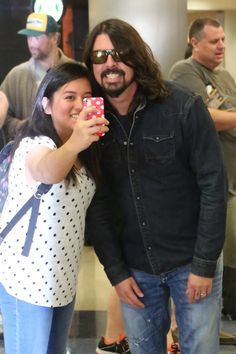 Say cheese! Foo Fighters frontman Dave Grohl takes a selfie with a fan at Los Angeles International Airport on March 24