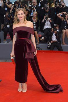 Diane Kruger con vestido de color burdeos con escote Bardot y gran lazada en el lateral, de Hugo Boss.