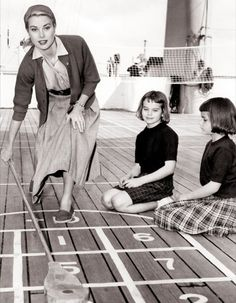 Grace Kelly playing shuffleboard with her nieces looking on. They are on board the ship (SS Constitution) en route to Monaco, for her wedding in 1956.