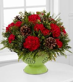 Merry Christmas Colander Flower Arrangement - 9 Stems - COLANDER INCLUDED. The Merry Christmas Colander Flower Arrangement is that unique gift you've been looking for this holiday season, set to spread Christmas cheer and joy with each magnificent bloom! Gorgeous red carnations and mini carnations offer unlimited color set against a bed of assorted holiday greens accented with natural pinecones to create an incredible and wonderfully fragrant holiday flower arrangement. Situated in a…