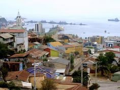View of Valparaiso Bay from one of the hills in a cloudy day, showing many of the precarious constructions and some of the warships of the Chilean Navy moored at the military docking facilities.