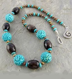 """The unique carved turquoise in this necklace pairs beautifully with gleaming, faceted brown agates and latte colored freshwater pearls. Even the sterling silver clasp is strikingly unique. The """"Ebb and Flow"""" necklace is sure to become one of your favorites!"""