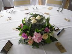 The table centres were a round arrangement of pink 'Sarah Bernhard' Peonies, Roses, Freesia, Tulips & Lilies with a goldfish bowl sat in the centre with floating candles sat on top of water.