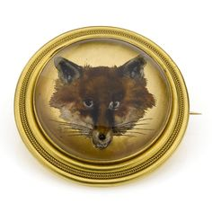 A Victorian reverse painted crystal intaglio brooch, finely carved to depict a fox's mask, C.1890
