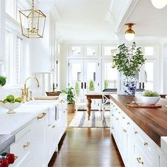 Amie Corley white kitchen with gold and brass hardware and walnut countertop