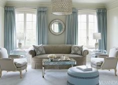 Lucite end tables, mirrored cocktaul table and awesome ottoman with great detail in living room by Suzanne_Kasler