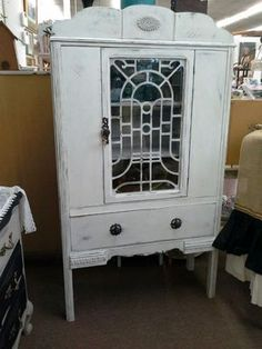 "$260 - This is an antique china cabinet that has been painted white and distressed. It has one center opening door with antique fret work still in place/ Once drawer in the base for additional storage. The cabinet measures 73"" x 14"" x 64"". It can be seen in Booth C1 at Main Street Antique Mall, 7260 E Main St, Mesa, AZ 85207 - Open 7 days a week 10a.m. to 5:30p.m."