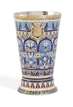 A Russian silver-gilt and cloisonné enamel beaker, Ovchinnikov, Moscow, 1894, the surface decorated with formal foliage in ogee arches within bands of geometric motifs, white bead borders, the front applied with the civic arms of St Petersburg.