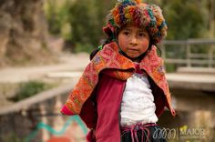 Located in the Andes town of Huilloc, a young Peruvian girl displays her colorful, woven clothes that were made in her weaving community. Photo by MajorMultimedia.com
