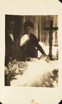 "Ghostly mourning scene, c 1920 by William Hope, ""spirit photographer"" A woman mourns for her husband in a Chapel of Rest, the woman's son stands beside her.  The image of a man's face has been superimposed over the original photograph. The spirit album notes that the family were Roman Catholics and believed in life after death."