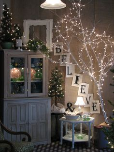 Beautiful Christmas decor made with tree branches spray painted white & little white Christmas lights. The little lamp on the table helps to accent the whole scene. Burlap Christmas, Noel Christmas, Winter Christmas, Christmas Decorations, Cottage Christmas, Country Christmas, Simple Christmas, Light Decorations, Christmas Vignette