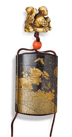 A four-case lacquer inro by Togyoku Meiji period, late 19th century  decorated in gold hiramaki-e with butterflies in flight above flowering chrysanthemum and bound grasses, on a roiro-nuri ground with hirame, signed Togyoku; with an ivory netsuke carved with a man seated in front of a small boy, signed Hansei and coral ojime, wood storage box 8.5 cm long