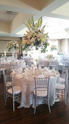 Silver wooden chiavari chairs with white cushions, floor-length silver bichon satin table cloths, and unique centerpieces of varied heights using hydrangeas, gladiolas, peonies, and roses in blush, white, and ivory colors creates the most elegant, soft, and classic wedding reception settings. ~Avalon Manor, Merrillville, Indiana