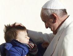 Pope Francis greets a child as he arrives to lead his general audience in St. Peter's Square at the Vatican Dec. 4.