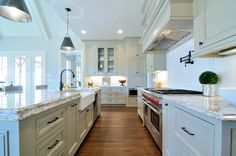 Traditional Kitchen with Custom hood, Kitchen island, Galley, Pendant light, Stone Tile, French doors, Inset cabinets