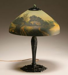 Antique Reverse Painted table lamp. Typical scene and shape of shade. Some are signed and some are not. Metal allow base, often pot metal or zinc with a bronze finish. Electric lamps like this were made c.1915-35 by numerous US companies.