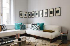 Dans le salon, un canapé fait sur mesure agrémenté de coussins de la galerie Alberto Levi, à Milan. Sur la table basse, un Totem, un porte-plat, un vase et un porte-bougie de la Série Milanaise, le tout chez Oeuffice. Au mur, une série de tableaux du collectif d'artistes Rotor, et au sol, un tapis berbère.