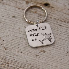 "Perfect for a pilot, flight attendant, or aviation fan! A thick 1"" metal square is hand stamped with the words ""come fly with me"" and paired with our exclusive airplane image. Items ship within 2 weeks and come boxed, ready for gift giving.This design is a copyrighted TheRustedChain original ©."