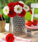 A vase inside a cheese grater makes for a beautilul outdoor flower centerpiece.