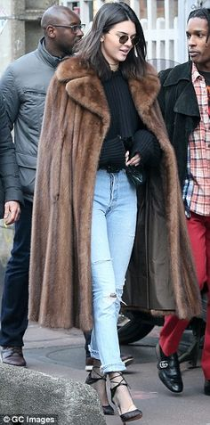 Cheeky! The 21-year-old flashed her toned midriff for all to see in vintage-style jeans - which she layered trendily over a pair of fishnet tights for her glamorous day out