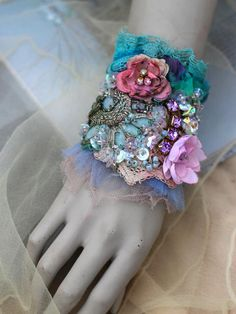 Bold ornate wrist wrap, shabby chic, bohemian inspired; is made of vintage & antique laces and trims, - handmade linen bobbin lace, painted silks, soft tulle;- stitched, textured, embroidered. Cuff is adorned with vintage metallic embroidery detail, vintage blooms, torn tulle, rich beading with clear and dusty blue seed beads, vintage ab sequins, and crystals. Fastens with a pair of vintage metal buttons; lined with silk. Measurements 18 cm wide about 11 cm high.The buttons are set for me...