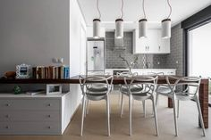 We are in love with this dining room. The modern vibe, the interconnectivity with the rest of the home, the plastic style chairs, the lamp shades. Everything is perfect! By Selecta HOME