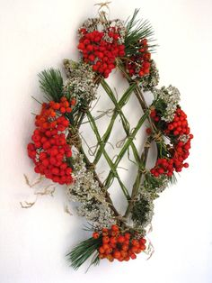 diamond shaped wreath made of flowers, berries and pine needles , with a center lattice made from the stems. This would look nice hanging on a window so that the glass showed through the lattice . http://ioluli.blogspot.it