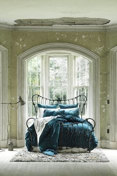 Shabby walls and an architectural bed with aquamarine comforter by Anthropologie | from Savor Home blog