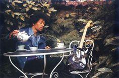 Jimi Hendrix with his guitar and tea.