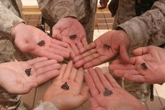 AT-TAQADDUM, Iraq (June 4, 2008) – Marines with 2nd Low Altitude Air Defense Battalion, Marine Air Control Group 28, 2nd Marine Aircraft Wing, hold their new ranks in their hands. They were all meritoriously promoted. Their mission in Iraq is to provide security for Camp Taqaddum and Camp Habbaniyah. (Photo by Lance Cpl. Robert C. Medina)