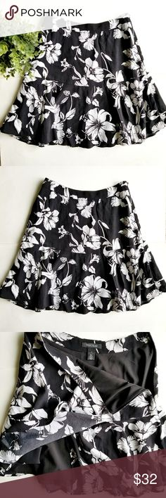 """White House  Black Market Floral Skirt Black and white floral A-line skirt with a ruffle bottom. Lined, side zipper closure. 14.5"""" waist,  20"""" long.  In excellent condition. White House Black Market Skirts"""