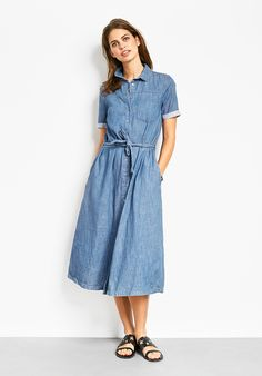 "This chic lightweight denim shirt dress is a Spring wardrobe staple. Pair with white plimsolls for a laid-back look, or with our Puket sandals for statement style. • Easy, straight fit. Try your usual size. • Button front with tie-belt at the waist. • Collared with short sleeves and cuffs. • Midi length, sits mid calf depending on height. • Model is 5'9"" and wears size 10."