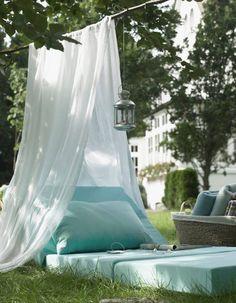 Coin sieste dans le jardin via un matelas de sol surplombé d'un ciel de lit