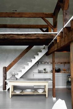 A kitchen tucked under a white-painted staircase in a Scandinavian home