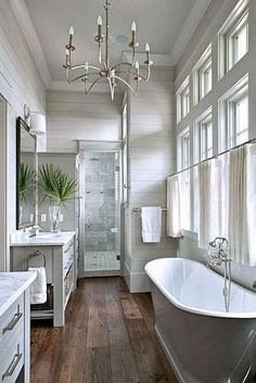 Beautiful Bathrooms these seven beautiful bathrooms are reminiscent of day spas Beautiful Bath Rustic Wood Floors Shiplap Chandelier Grey Vanity