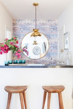 Feminine home bar with gorgeous gold floral pendant light, pattern wall, and large round gilded mirror