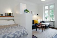 corner sofa in dark blue, with white and yellow cushions, and two small coffee tables, living room furniture for small spaces, sleeping area separated by a white wardrobe #HomemadeFurnitureIdeas