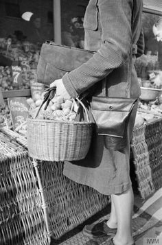 A DAY IN THE LIFE OF A WARTIME HOUSEWIFE: EVERYDAY LIFE IN LONDON, ENGLAND, 1941 ~ A close up view of Mrs Day's shopping basket and gas mask case, which she has taken with her on her shopping trip. The gas mask case has a special pocket which enables it to be used like a handbag. Behind her, the greengrocer arranges his wares. This photograph was probably taken on the King's Road in Chelsea.