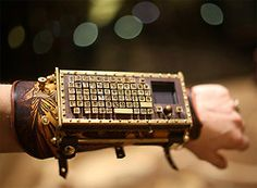 """""""This awesome device is a fully-functional Typewriter Arm Guard with Bluetooth and Touchpad created by Thomas Willeford of Brute Force Studios. The keyboard is mounted on an intricately tooled Steampunkish leather and brass arm guard."""""""