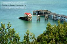 """Mumbles Pier by Lynda Wilks. """"Taken from high on the headland, this shot of the iconic red-roofed boat house might one of the last. Builders are currently busy at work constructing a new life-boat house, and renovating Mumbles Pier. The old boat is house is a listed building, however, and will be kept, possibly as a Visitor Centre."""""""