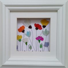 Tiny pieces of genuine Cornish sea glass have been used to create these colourfully painted flowers set inside a 20cm x 20cm glazed box frame.