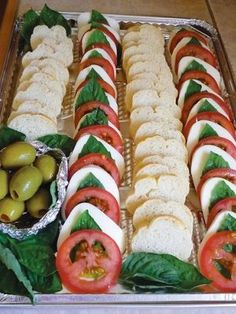 Gorgeous platter with rows of baguette rounds next to rows of tomato, mozzarella, basil and drizzled olive oil.