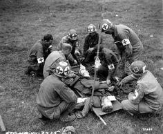 """medics attend an injured person lying in a stretcher. medical staff of the 79th ID (USD) Note that the crosses on the helmets are painted or stenciled by hand and the medic from right to directly painted his """"cuff"""" on his jacket M-41. Sue the same medic badge """"division at the Cross of Lorraine"""" A blue shield embroidered in white with a white cross of Lorraine"""