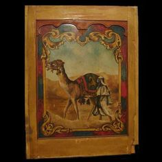 """Carousel Panel, The Sheik - $1050  Reflecting the popular culture of the 1920s and its enchantment with the Middle East as reflected in the Rudolph Valentino movie """"The Sheik"""" and the jazz rendition of """"The Sheik of Araby,"""" this wood framed carousel panel is hand painted in warm tones on canvas depicting an Arab prince in flowing robes striding along beside his """"ship of the desert.""""  76.5 high x 57.5 wide."""
