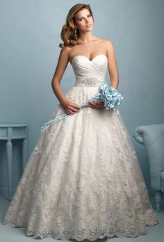 Allure Bridals. For the bride who wants everything %u2014 this strapless ballgown features a pleated bodice and crystal detailing, along with a lace applique overlay.